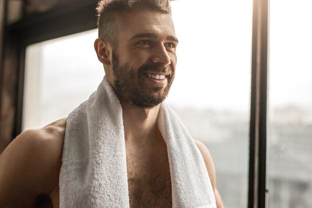 ジムでのフィットネストレーニングの休憩中に笑顔で窓から目をそらしているタオルで陽気な上半身裸のスポーツマン
