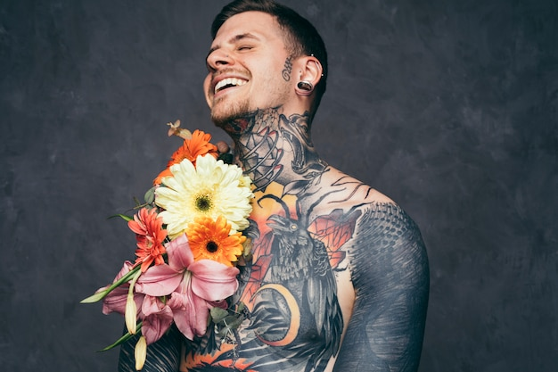 Cheerful shirtless young man with pierced ears with flower decoration on his tattooed body
