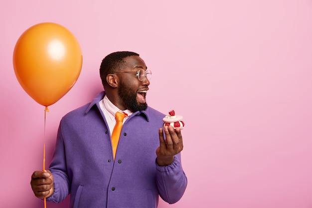 Allegro uomo afroamericano scioccato sta con palloncino festa e dolce dessert