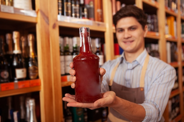 Cheerful shopkeeper smiling holding out bottle to the camera, copy space