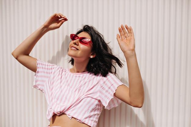 晴れた日を楽しんでいる陽気な短髪の女性。テクスチャード加工の背景に手を上げて立っているサングラスでリラックスした女性モデル。