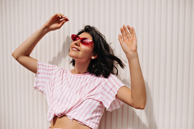 Cheerful short-haired woman enjoying sunny day. relaxed female model in sunglasses standing with hands up on textured background.