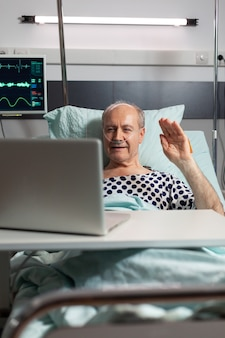 Cheerful sick senior man waving at camera during video conference using laptop laying in bed, breathing through oxygen tube. man recovering after surgery and treatment.