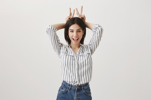 Веселая глупая девушка показывает жест кроличьих ушей за головой и улыбается