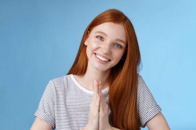 陽気な誠実な親切な赤毛の女の子は、頭を傾けてコケティッシュな目をします。