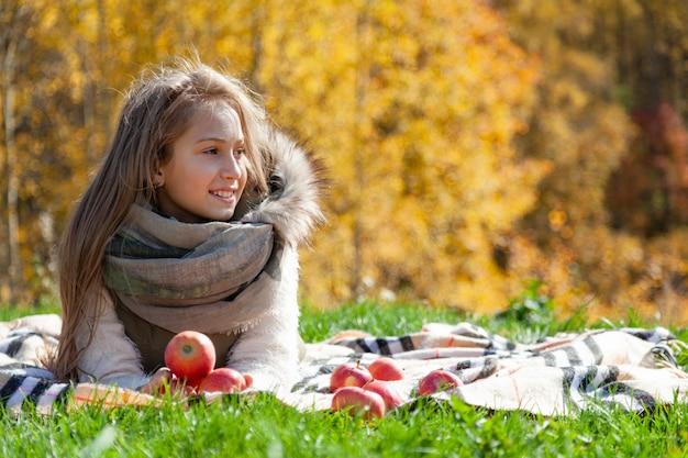 秋のピクニックにリンゴを保持している陽気な姉妹