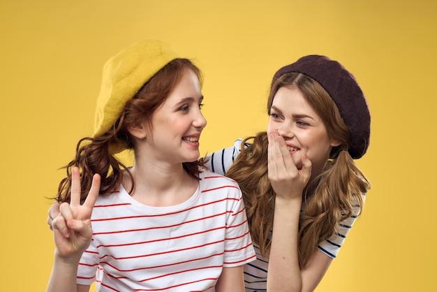 帽子の縞模様のtシャツの陽気な姉妹はライフスタイル黄色の背景の家族を喜びます。高品質の写真