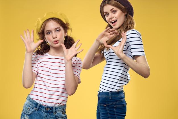 帽子の縞模様のtシャツの陽気な姉妹はライフスタイル黄色の家族を喜ばせます