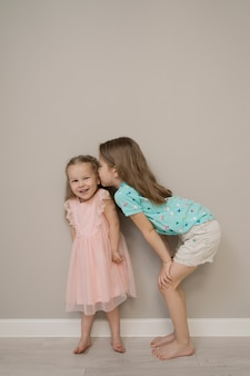 Cheerful sisters moments on beige background