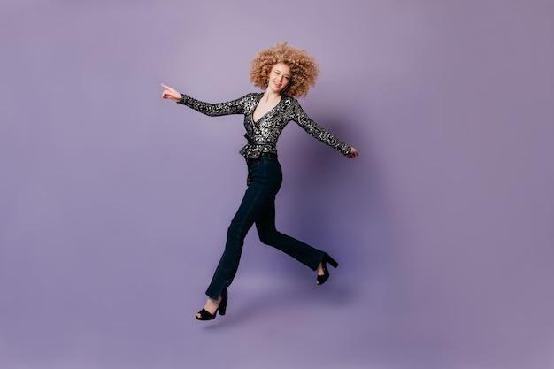 ライラックの空間にジャンプするスタイリッシュなジーンズとディスコブラウスの陽気なほっそりした女性。