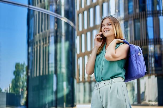 쾌활한 슬림 여성이 야외에서 전화로 친구와 이야기합니다.