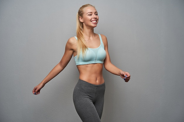 Cheerful slim young long haired blonde woman jumping over light grey background and looking happily ahead, demonstrating her perfect white teeth, training hard before work
