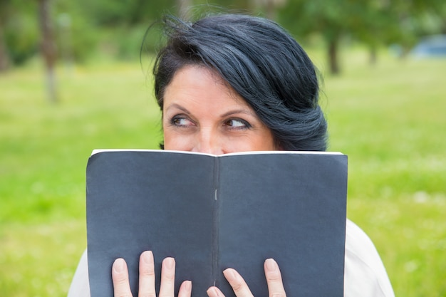 Cheerful sly woman hiding face behind open diary