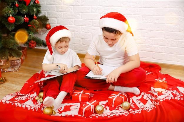 クリスマスの帽子をかぶっているクリスマスの小さな子供たちの家で陽気な小さな男の子