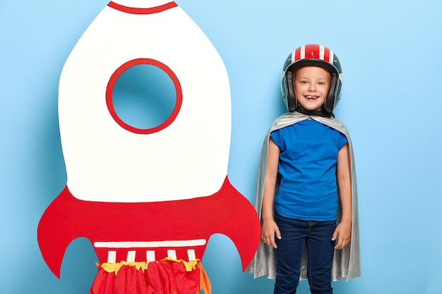 Cheerful small child wears helmet and grey cape, stands near paper craft rocket, wants to fly in space