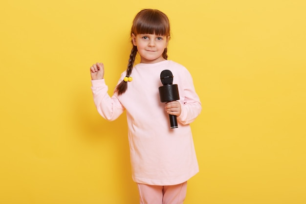 Cheerful small female kid with dark hair and pigtails standing against yellow wall with microphone in hands, singing song or speaks, and showing clenched fists.