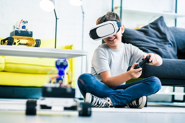 Веселый умный улыбающийся мальчик сидит на полу, держа пульт и тестируя своего робота