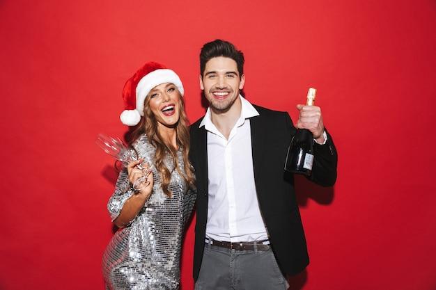 新年を祝って、赤いスペースの上に孤立して立っている陽気なスマートな服を着たカップル