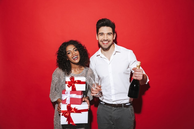 Cheerful smartly dressed couple standing isolated over red space, celebrating new year