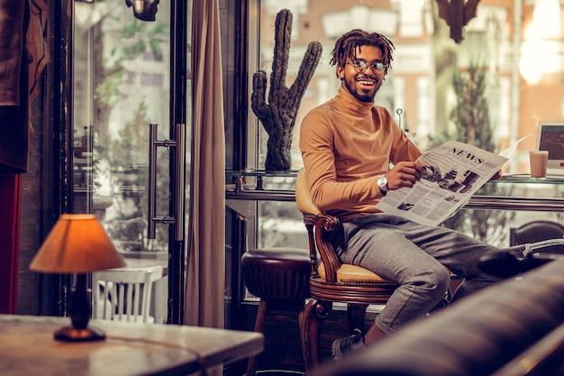 陽気な笑顔。レトロな椅子に座って幸せを感じて喜んでいる男性