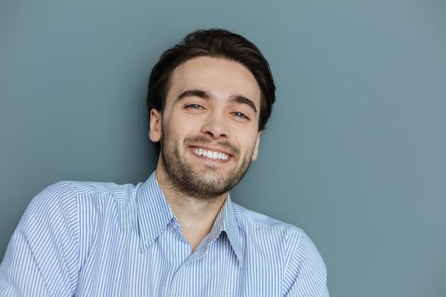 陽気な笑顔。素敵な気分で笑っている素敵なハンサムな若い男の肖像画