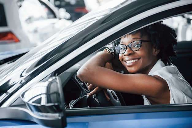 Cheerful smile. young african american woman sits inside of new modern car.