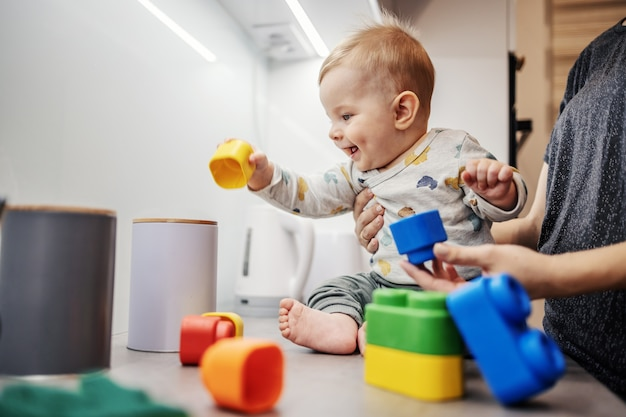 Cheerful smiling adorable little boy sitting on kitchen counter and playing with building blocks with his mother.