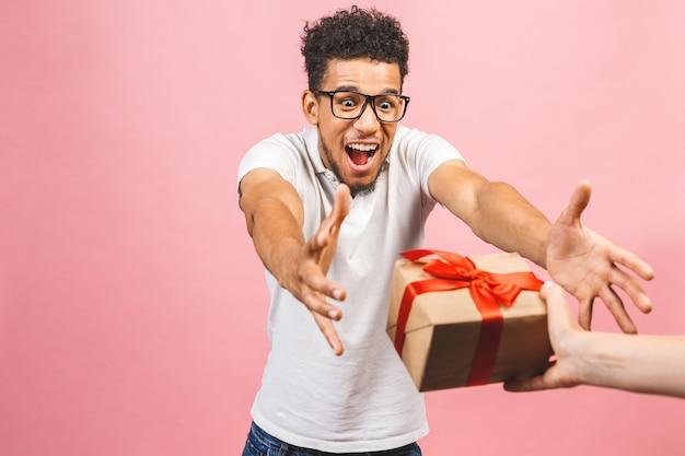 Веселый улыбающийся афро-американский тысячелетний парень в очках, держащий упакованную подарочную коробку.