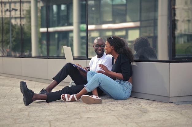 地面に座って、昼間にラップトップを使用して陽気な笑顔のアフリカの男性と女性