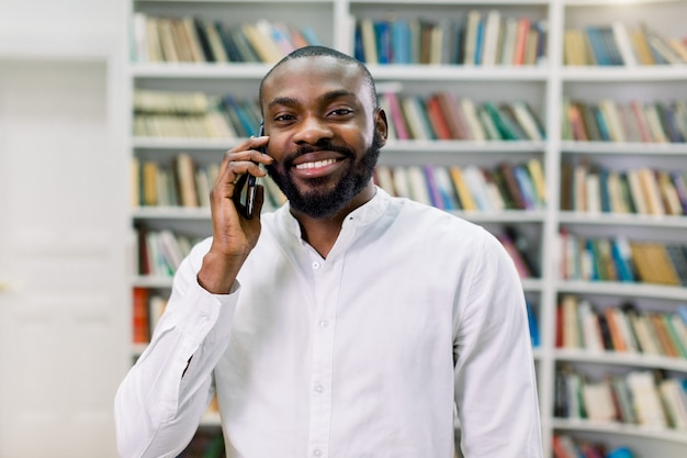 Cheerful smiling african male student or businessman, wearing white shirt, talking on the phone, standing in modern library