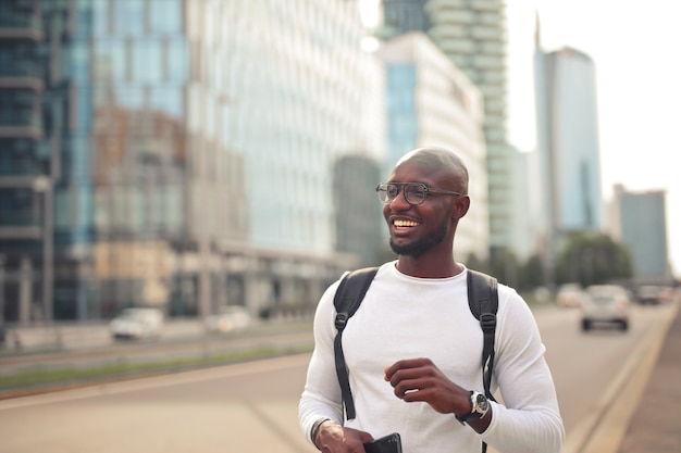 Allegro sorridente maschio africano con gli occhiali che indossa una maglietta bianca e uno zaino all'aperto