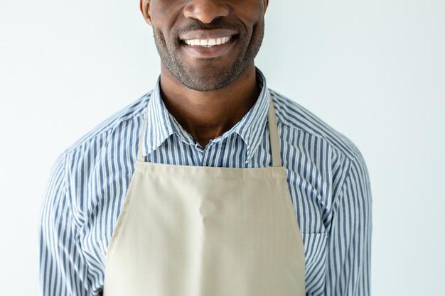 Веселый улыбающийся афро-американский бариста, стоящий у белой стены