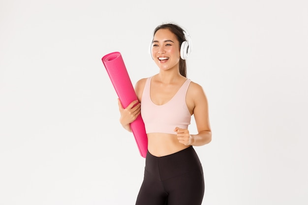 Cheerful smiling asian fitness girl in headphones and sportswear going to gym with rubbermat, hurry up for yoga classes excited,