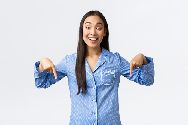 쾌활하게 웃고 있는 아시아 소녀는 파란색 잠옷을 입고 서 있는 것처럼 손가락을 아래로 가리키고, 잠자는 파티에서 여자 친구에게 멋진 것을 보여주고, 발표하고, 흰색 배경을 만드는 멋진 소식에 반응합니다.