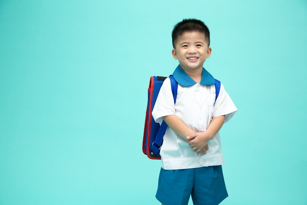Cheerful smiling asian little boy in a school uniform with backpack having fun isolated on green wall, first day of kindergarten and back to school concept