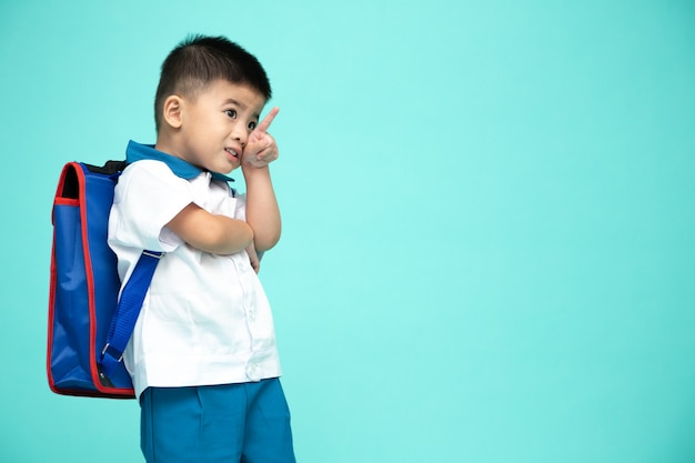 Cheerful smiling asian little boy in a school uniform with backpack pointing up on copy space isolated on green wall, first day of kindergarten and back to school education concept
