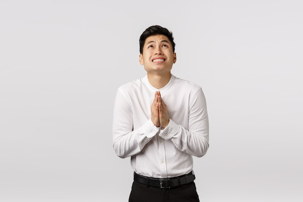 Cheerful smiling asian young entrepreneur with white shirt praying