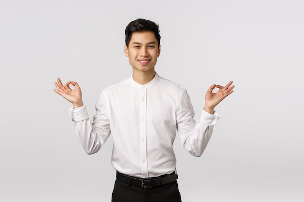 Cheerful smiling asian young entrepreneur with white shirt relieved