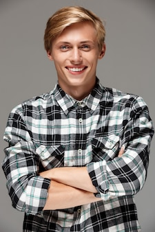 Cheerful smiling blond handsome young man wearing casual plaid shirt with hands crossed on chest on grey wall