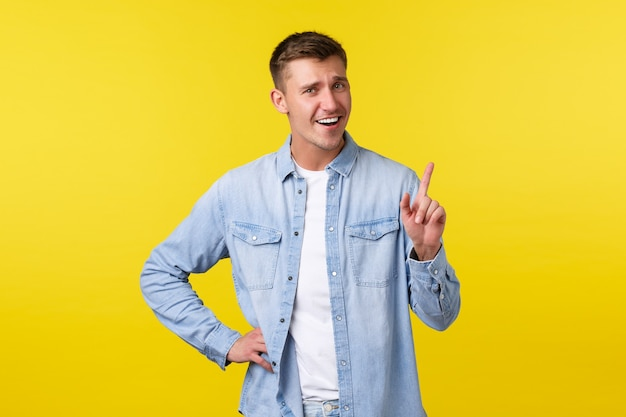 밝은 미소의 금발 남자가 손가락을 흔들고, 너무 빨리 말하지 말고, 누군가를 꾸짖거나, 잠시만 기다리라고, 노란색 배경에 낙관적으로 서서 맨 위에 광고를 표시합니다.