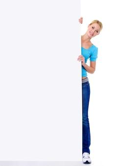 La donna bionda sorridente allegra guarda fuori a causa di un'insegna di carta vuota