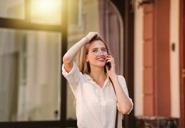 屋外で電話で話している陽気な笑顔のブロンドの女性
