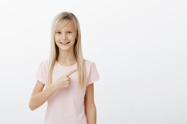 右上隅を指している陽気な笑顔のブロンドの女の子