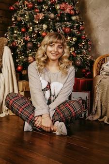 명랑 웃는 금발의 여자는 공 크리스마스 시간 해피 홀리데이 크리스마스 트리 새해 깜짝 선물 크리스마스 트리를 장식
