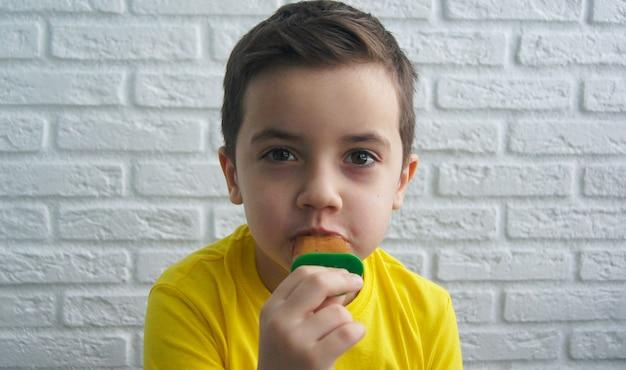 Веселый улыбающийся мальчик ест мороженое на фоне кирпичной стены