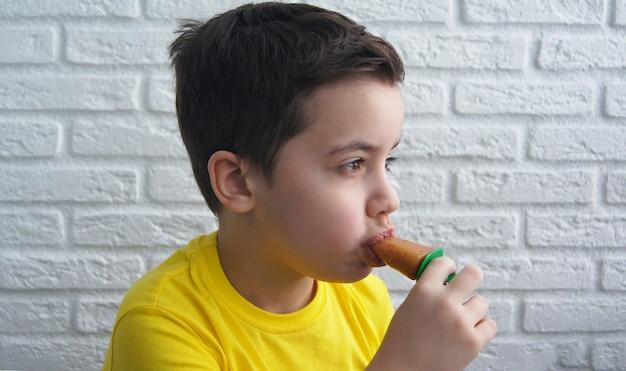 Веселый улыбающийся мальчик ест сорбет мороженого на фоне кирпичной стены