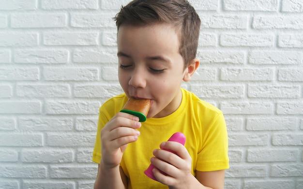 Веселый улыбающийся мальчик ест сочный ледяной сорбет на фоне кирпичной стены