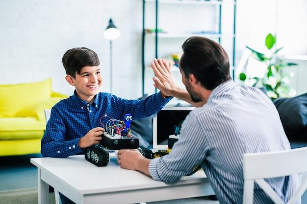 エンジニアリングを楽しみながら父親にハイタッチを与える陽気な笑顔の少年