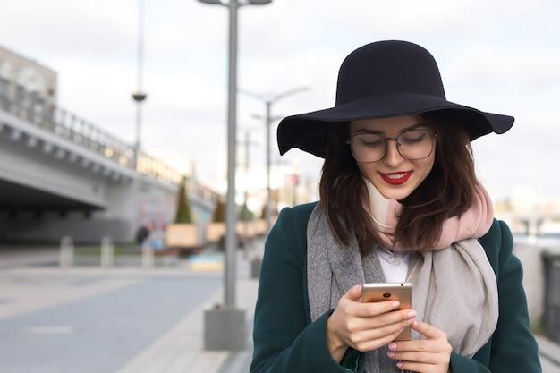 携帯電話を使用してファッショナブルな服を着たメガネと帽子の陽気な笑顔のブルネットの女の子
