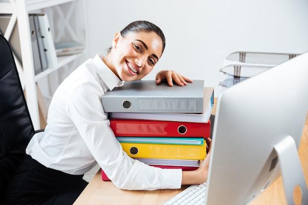 Веселая улыбающаяся деловая женщина кладет голову на стопку красочных папок, сидя за офисным столом